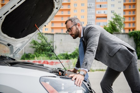 side view of handsome businessman leaning on open car hood Фото со стока