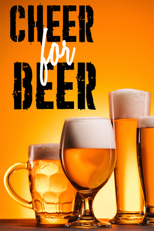 arranged mugs of cold beer with froth on orange background with cheer for beer inspiration