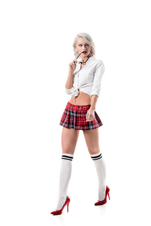 sexy young woman in short schoolgirl plaid skirt and knee socks with eyeglasses posing isolated on white Banque d'images - 109769129