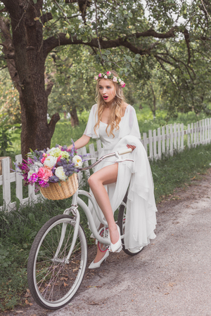 beautiful shocked young blonde bride riding bicycle with flower basket