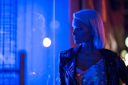 stylish young woman in glossy tank top and leather jacket on street at night under blue light