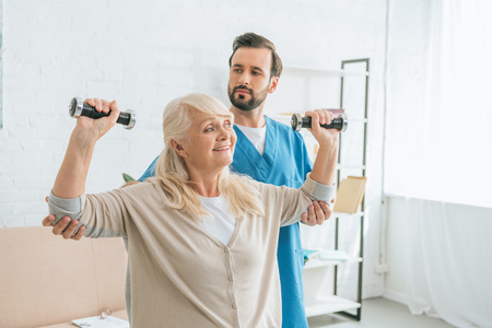 social worker looking at smiling senior woman training with dumbbells