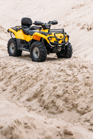 modern yellow all-terrain vehicle standing in desert
