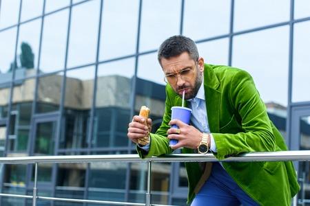 portrait of man in green velvet jacket with french hot dog drinking soda drink on street Banco de Imagens