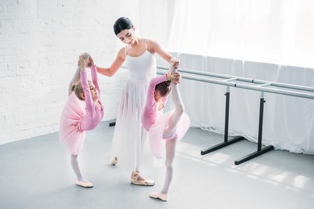 smiling young ballet teacher exercising with kids in ballet school