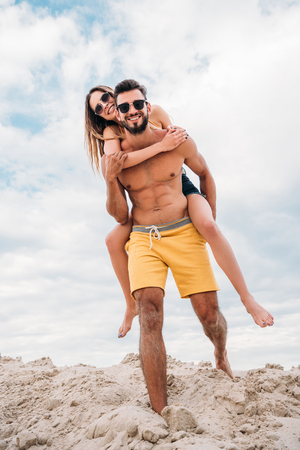 attractive young woman piggybacking on boyfriends back at beach