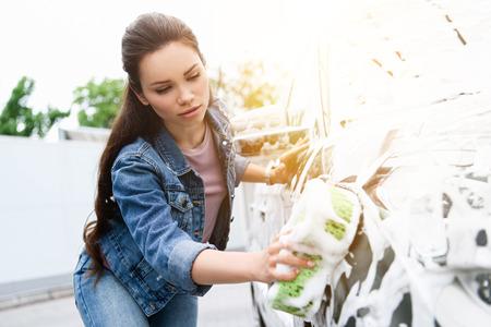 schöne Frau, die Auto an der Autowäsche mit Lappen und Schaum putzt