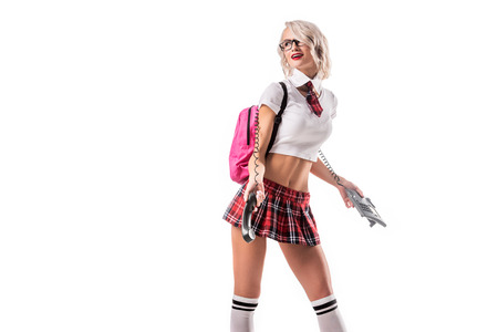 blond woman in seductive schoolgirl uniform with pink backpack and telephone isolated on white Stockfoto