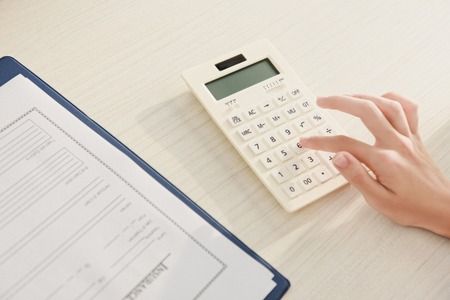 cropped view of woman counting finances on calculator at table with insurance claim form Stok Fotoğraf