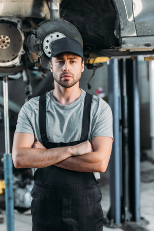 serious mechanic posing with crossed arms in auto repair shop