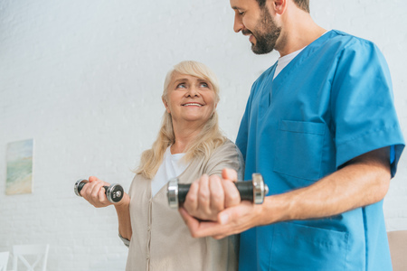 cropped shot of social worker helping smiling senior woman exercising with dumbbells Banco de Imagens