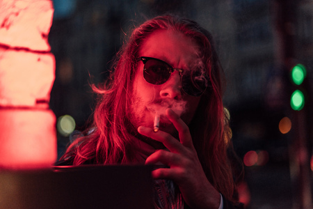 handsome young man in sunglasses smoking cigarette under red light on street