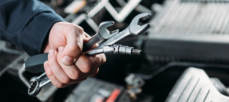partial view of worker holding tools and wrenches in hand Stock Photo
