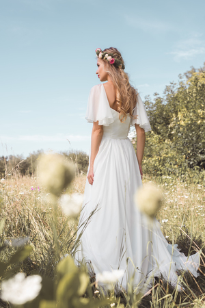 back view of beautiful young bride in wedding dress and floral wreath walking on field