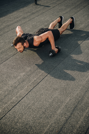 handsome sportsman doing push ups with dumbbells on roof Stock Photo