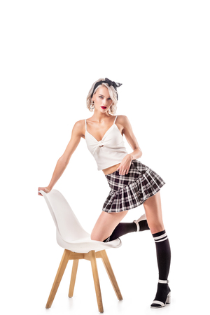 sexy woman in schoolgirl clothing and knee socks on chair isolated on white Stockfoto
