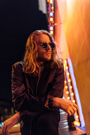 handsome young man in leather jacket and sunglasses on street at night under yellow light