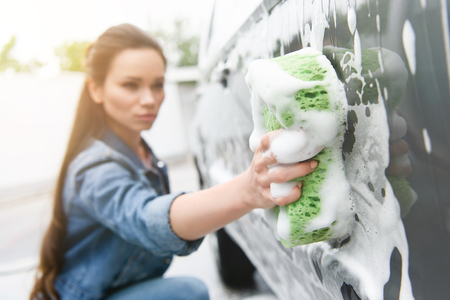 attractive woman cleaning car at car wash with rag and foam Imagens