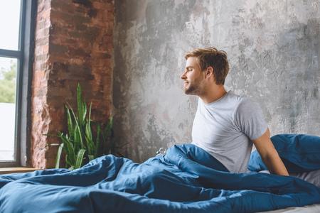 knappe jongeman wakker in zijn bed 's ochtends thuis