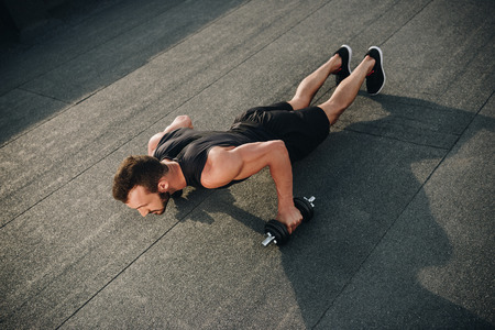 high angle view of handsome sportsman doing push ups with dumbbells on roof