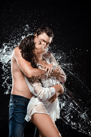 portrait of sexy couple swilled with water isolated on black
