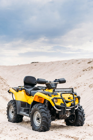 modern yellow all-terrain vehicle standing in desert on cloudy day