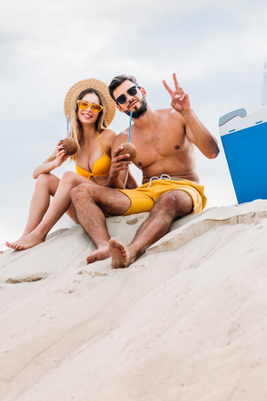 bottom view of young couple with coconut cocktails sitting on sand in front of cloudy sky and showing peace gesture Stock Photo