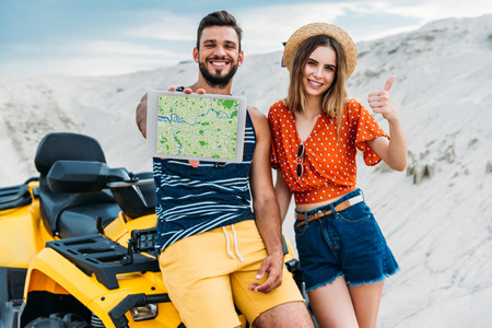 beautiful young couple with atv showing digital tablet with navigation website on screen and thumb up at desert