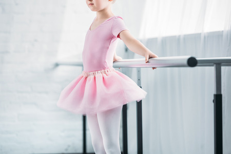 cropped shot of kid in pink tutu practicing ballet in studio