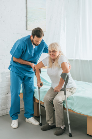 male nurse helping senior woman with crutches sitting on hospital bed
