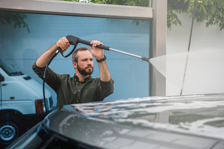 handsome man cleaning car at car wash with high pressure water jet Archivio Fotografico
