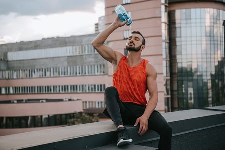 handsome sportsman pouring water from bottle on face on roof