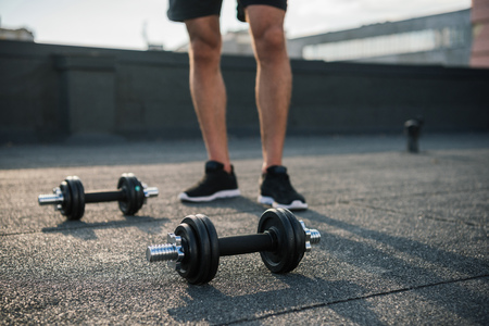 cropped image of sportsman standing near dumbbells on roof