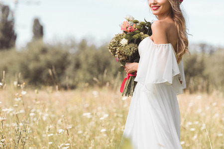 cropped shot of smiling young bride in white dress holding wedding bouquet outdoors