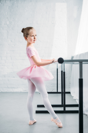 side view of little child in pink tutu practicing ballet in ballet school