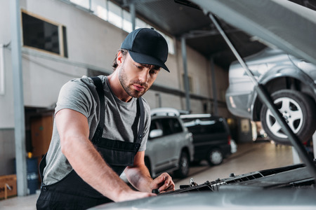 manual worker in overalls repairing car in mechanic shop 스톡 콘텐츠