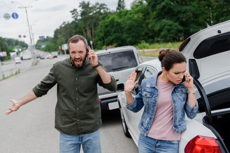 irritated drivers talking by smartphones on road after car accident