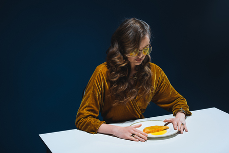 portrait of woman in luxury clothing sitting at table with meat pastry on plate with blue backdrop Stock Photo