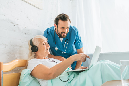 smiling male nurse looking at happy senior woman in headphones using laptop in hospital bed