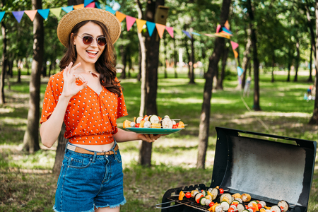 portrait of happy woman in hat and sunglasses with grilled vegetables on plate showing ok sign in park