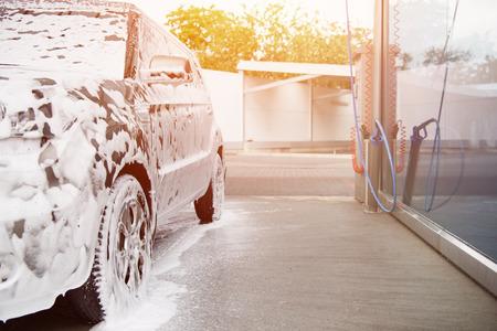 Coche en espuma limpiadora blanca en el lavado de coches durante la puesta de sol Foto de archivo - 109800348