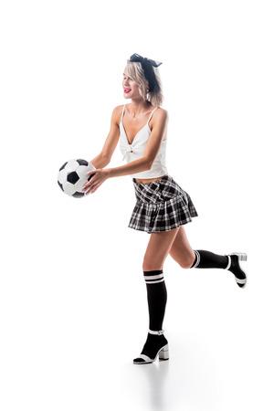 sexy woman in plaid schoolgirl skirt and black knee socks with football ball isolated on white