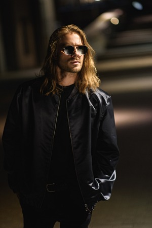 attractive young man in sunglasses and leather jacket on city street at night