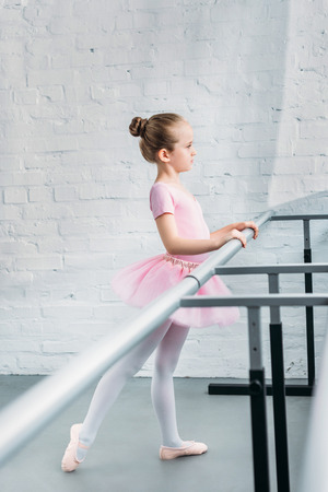 side view of beautiful little ballerina practicing ballet in studio