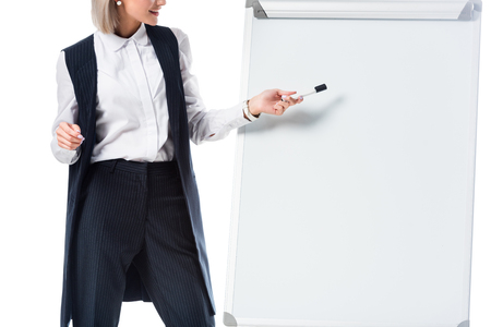 partial view of businesswoman in formal wear pointing at empty whiteboard isolated on white