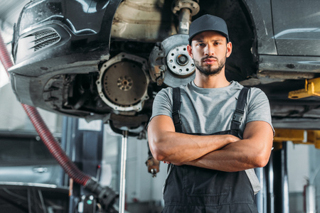 confident mechanic posing with crossed arms in auto repair shop