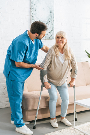 male nurse supporting smiling senior woman with crutches Stock Photo