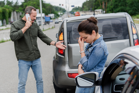 upset man and woman near cars after car accident Stock Photo