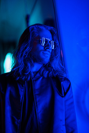 attractive young man in sunglasses under blue light on street at night 스톡 콘텐츠