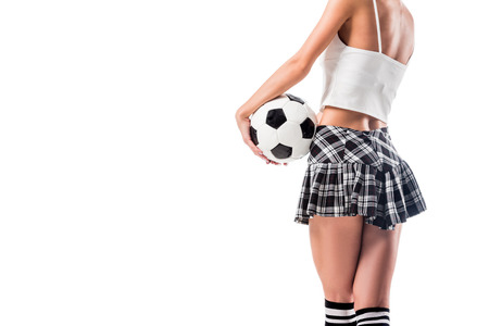 cropped shot of sexy woman in plaid schoolgirl skirt holding football ball isolated on white